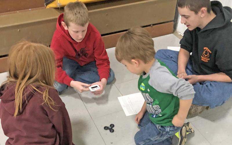 Strain-Japan students, Jordyn,Nolan, Ayden, and Wyatt intently watching and timing Ayden's fidget spinner spin.