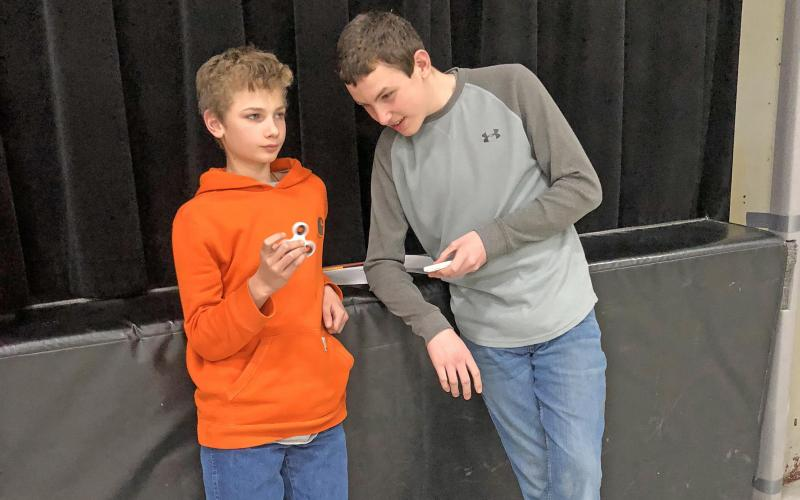 Johny spins his fidget spinner while Ben times the spin at the Strain-Japan STEM activity.