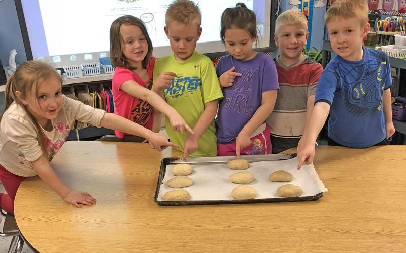 THE KINDERGARTEN STUDENTS from Strain-Japan pointing out their own loaves of bread ready to rise.
