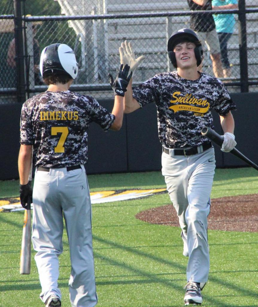 Garrett Juergens and Collin Immekus exchange high fives after Juergens scores in the first inning Friday